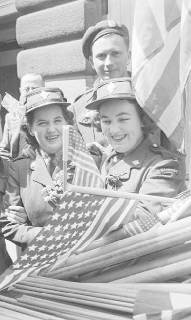 Soldados canadenses e integrantes do Exército de Mulheres Canadenses compram bandeiras para comemorar o Dia da Vitória na Inglaterra HANDOUT / REUTERS