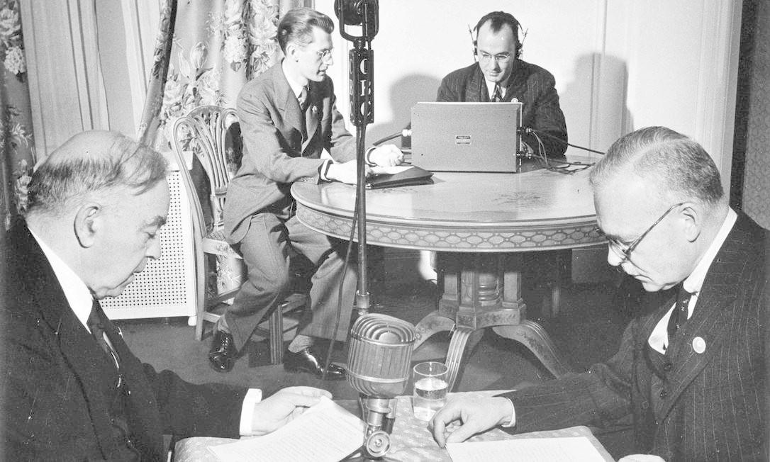 O primeiro-ministro canadense William Lyon Mackenzie King e o ministro da Justiça candense Louis St. Laurent recebendo uma mensagem durante o Dia da Vitória HANDOUT / REUTERS