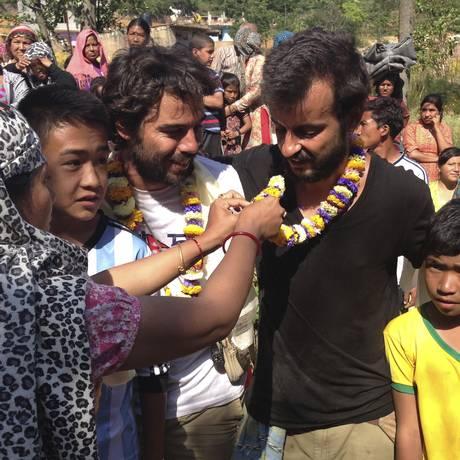Portugueses Lourenço Macedo santos (de preto) e Pedro Queirós (de branco) recebem colares florais de moradores do vilarejo de Ichangu Narayan, nos arredores de Katmandu Foto: Johnson Lai / AP