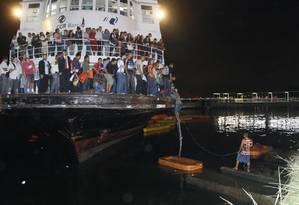 Após cerca de uma hora presos em barca, passageiros usam corda para chegar ao bote de resgate Foto: Marcelo Carnaval / Agência O Globo