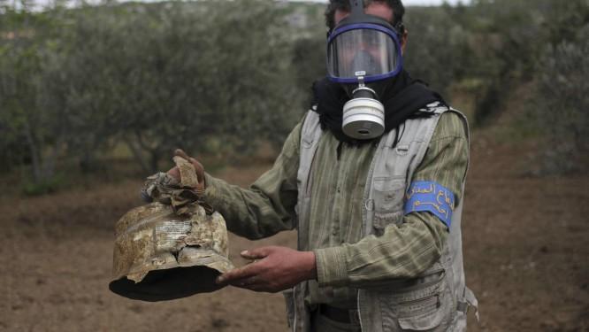 Usando máscara, membro da Defesa Civil carrega cápsula que teria sido usada em ataque com gás de cloro na região de Idlib Foto: Abed Kontar / REUTERS