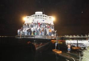 Passageiros descem da embarcação com a ajuda de cordas Foto: Marcelo Carnaval / Agência O Globo