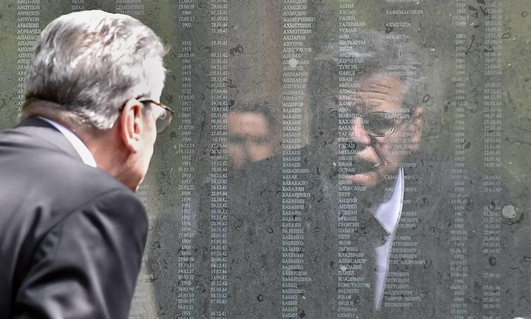 Presidente alemão Joachim Gauck refletido no memorial da guerra com os nomes de prisioneiros de guerra russos no cemitério soviético em Schloss Holte-Stukenbrock, no Oeste da Alemanha Martin Meissner / AP