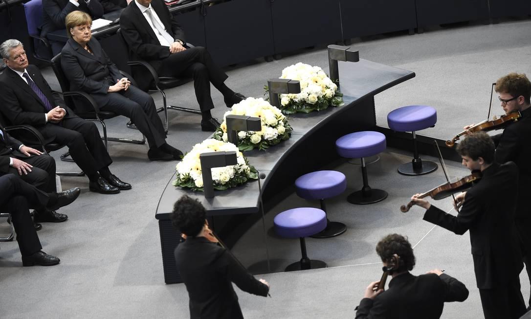 Joachim Gauck e a chanceler da Alemanha Angela Merkel assistem a apresentação de músicos sentados em frente às flores durante a cerimônia no parlamento alemão ODD ANDERSEN / AFP