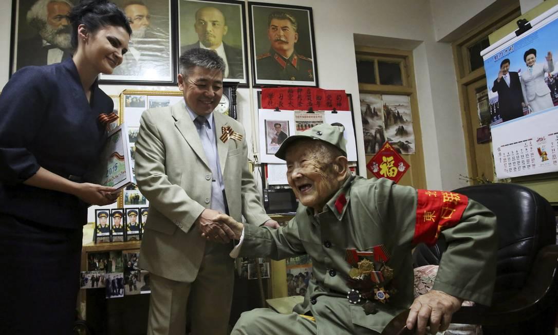 Lu Baoping, um veterano chinês de 97 anos, que lutou contra os japoneses durante a guerra, cumprimenta um diplomata russo enquanto recebe uma medalha comemorativa CHINA STRINGER NETWORK / REUTERS
