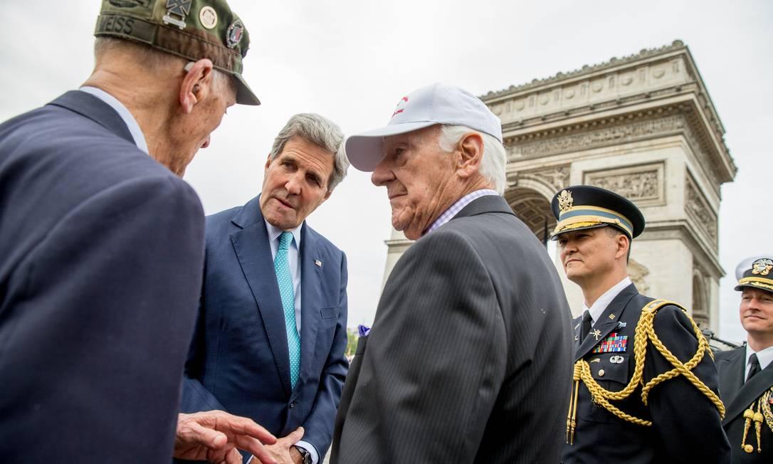 Secretário de Estado dos EUA John Kerry cumprimenta veterano Arthur Staymates, de 89 anos, na esquerda, e Stephen Weiss, de 90, no centro, após uma cerimônia no Túmulo do Soldado Desconhecido, em Paris, na França Andrew Harnik / AP