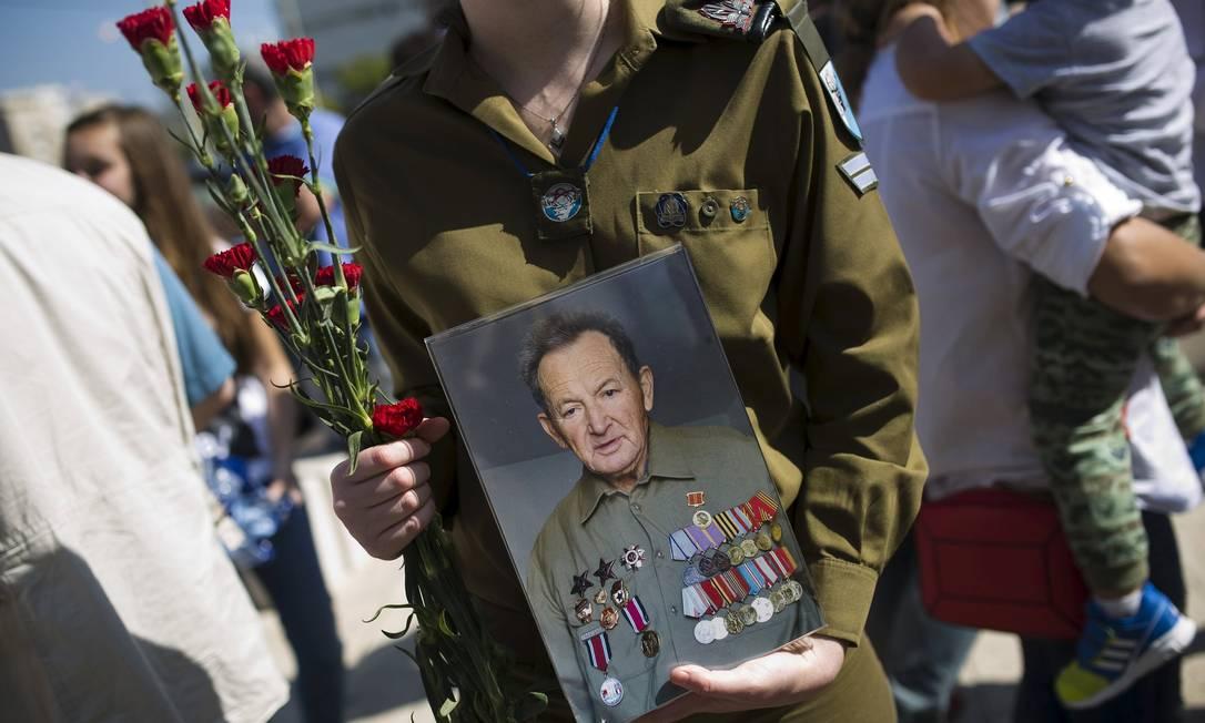 Um soldado israelense segura a foto de um veterano da Segunda Guerra durante uma parada que marca o dia da vitória dos Aliados sobre a Alemanha nazista, na cidade de Ashdod, em Israel AMIR COHEN / REUTERS