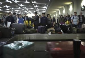 Passageiros esperam suas malas no aeroporto de Pyongyang, na Coreia do Norte. Foto: Wong Maye-E / AP
