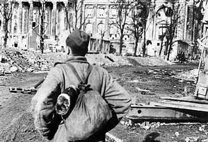 Destruição. Soldado soviético, no final da guerra, em frente ao prédio do Reichstag, o parlamento alemão, destruído em Berlim Foto: A MOROZOC / AFP
