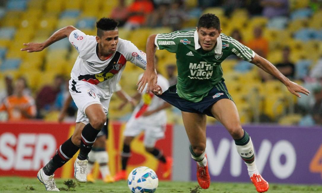 Edson arranca com a bola pelo Fluminense e temo calção puxado por Naldo, do Joinville: falta! Pedro Kirilos / Agência O Globo