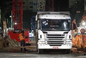 Funcionários fazem a limpeza do caminhão, após descarregamento de material Foto: Thiago Lontra / Agência O Globo