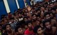 Um imigrante bangalês levanta a mão para pedir roupas nas instalações da polícia da Malásia. Cerca de 2000 pessoas foram resgatadas por autoridades malásias e indonésias em dois dias, sendo mais da metade na ilha malaia de Langkawi.