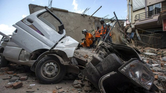 Policiais observam carro atingido por casa que desabou no centro de Katmandu Foto: ATHIT PERAWONGMETHA / REUTERS