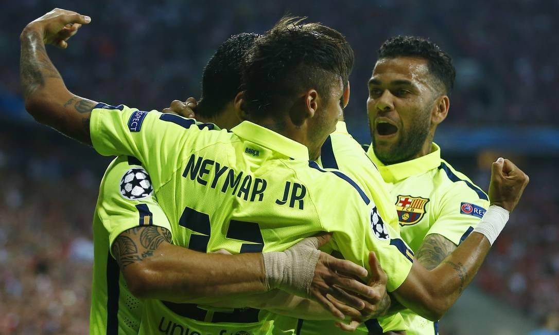 Neymar recebe o abraço dos companheiros do Barcelona, entre eles o também brasileiro Daniel Alves (à direita), após o 2º gol que o atacante marcou contra o Bayern Matthias Schrader / AP