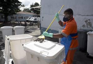 No Hospital Rocha Faria, em Campo Grande, gari lava as lixeiras: Comlurb foi chamada para ajudar na retirada de montanhas de lixo nos corredores e salas Foto: Márcia Foletto / Agência O Globo