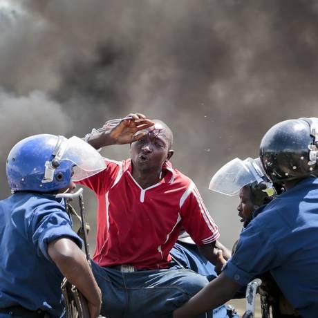 Manifestante ferido é detido pela polícia em Bujumbura após o anúncio da tentativa de golpe no Burundi Foto: Gildas Ngingo / AP