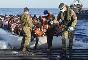 Soldados da Marinha italiana ajudam imigrantes a desembarcar Foto: Crown Copyright/Carl Osmond / REUTERS
