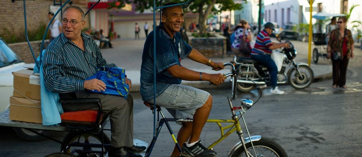 Emilio Cueto num bicitáxi em Camaguey: ele distribui seus livros sobre a Virgem no país Foto: SARAH L. VOISIN / Sarah L. Voisin/The Washington Post