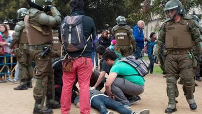 Estudantes ajudam um jovem baleado em Valparaiso Foto: Pablo Vanni/Reuters