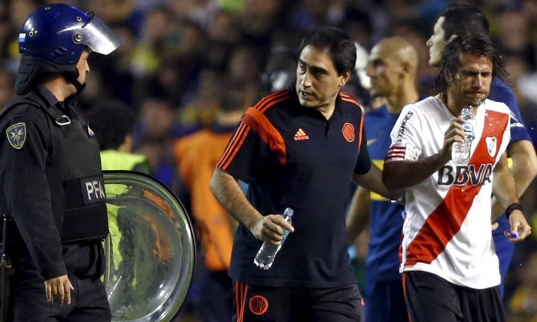 A polícia teve que proteger os jogadores do River na volta ao campo MARCOS BRINDICCI / REUTERS
