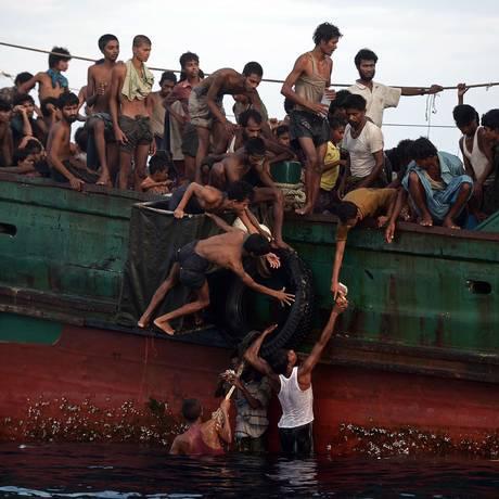Imigrantes rohingyas distribuem entre si pacotes de macarrão instantâneo jogados de helicóptero para barco abandonado pela tripulação no Mar de Andaman Foto: CHRISTOPHE ARCHAMBAULT / AFP