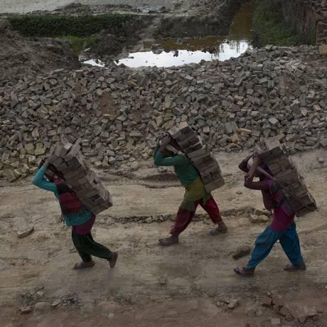 Nepaleses carregam tijolos em uma fábrica de Bhaktapur: cerca de 745 mil casas e edifícios foram danificadas ou destruídas pelos tremores que acometem o país desde abril Foto: Bernat Armangue/AP