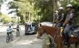 PMs a cavalo observam o movimento de ciclistas e visitantes num dos acessos ao parque onde houve ataques no início do mês