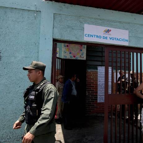 Um policial da Guarda Nacional Bolivariana supervisiona centro de votações em Caracas, na Venezuela Foto: Fernando Llano / AP