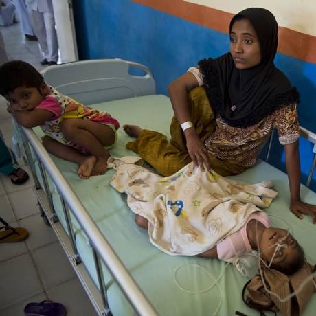 Mimi, uma imigrante rohingya, senta-se ao lado de sua filha gravemente desnutrida em um hospital na província de Aceh Foto: ROMEO GACAD / AFP