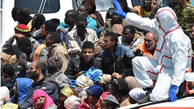 Equipes de resgate escoltam imigrantes ilegais no porto de Pozzalo, na Sicília. Especialistas acreditam que plano da UE para conter travessias do Mediterrâneo será muito caro e de difícil aplicação Foto: Carmelo Imbesi / AP
