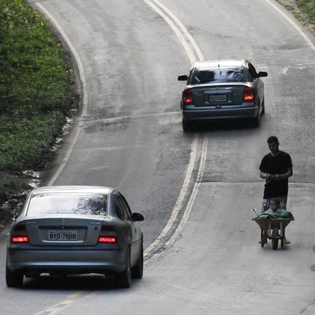 Homem carrega criança em carrinho de mão em avenida sem calçadas em Marsilac Foto: Michel Filho / Agência O Globo