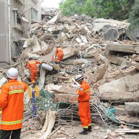 Equipe de resgate busca sobreviventes nos escombros de pédio de apartamento que desabou em Guiyang Foto: STR / AFP