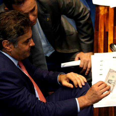O Senador Aécio Neves (PSDB-MG) segura nota de dólar com o rosto da presidente Dilma Rousseff depois de manifestantes contra o ajuste fiscal jogarem notas no Plenário Foto: Ailton de Freitas / Agência O Globo