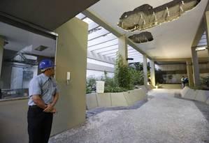 Um funcionário do Edifício Canoas observa um buraco aberto no teto da portaria durante a madrugada desta quarta-feira Foto: Pablo Jacob / Agência O Globo