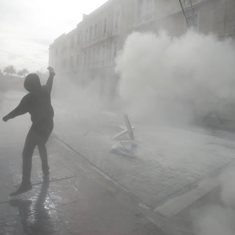 Um manifestante mascarado contra-ataca a polícia, que lançou gás lacrimogênio e jatos de água para conter os saques feitos no comércio local Foto: Luis Hidalgo / AP