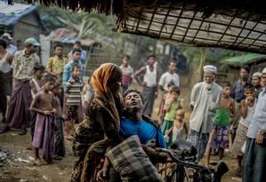 Um homem doente da etnia rohingya é amparado pela madrasta num campo de refugiados nos arredores de Sittwe, em Mianmar: minoria é alvo do extremismo budista Foto: TOMAS MUNITA / NYT