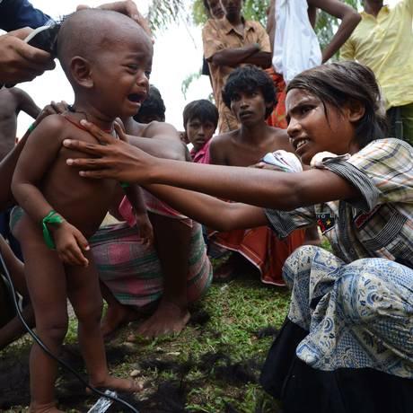 Voluntários cortam cabelo de crianças rohingyas na recém-criada criada área para imigrantes em Bayeun, na província indonésia de Aceh Foto: ROMEO GACAD / AFP