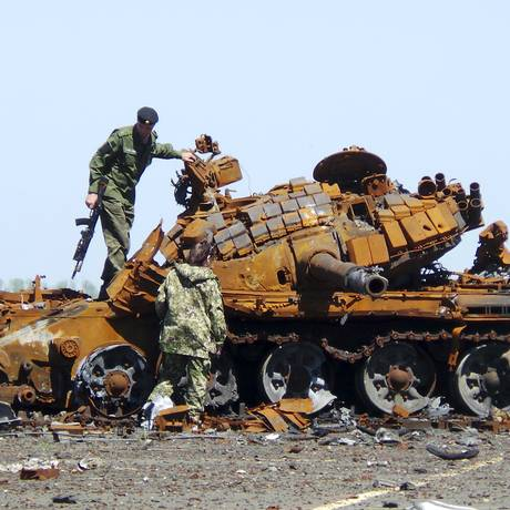 Separatistas pró-Rússia inspecionam um tanque queimado durante uma operação conjunta para procurar os restos de soldados mortos no aeroporto da cidade de Donetsk, na Ucrânia Foto: IGOR TKACHENKO / REUTERS