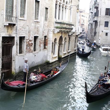 Turistas passeiam em gôndolas em Veneza Foto: Bloomberg News/ 8-10-2009