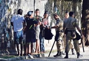 Jovens são revistados por guardas municipais na Glória, próximo ao local onde a chilena foi assaltada. Nada, porém, foi encontrado com o grupo, que acabou liberado Foto: Domingos Peixoto / Agência O Globo