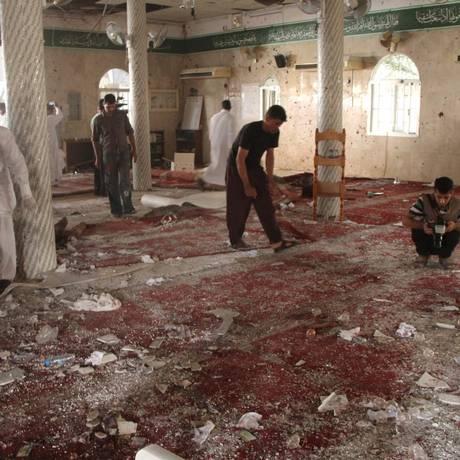 Pessoas examinam destroços deixados por ataque terrorista na última sexta-feira em mesquita xiita na Arábia Saudia Foto: STRINGER / REUTERS