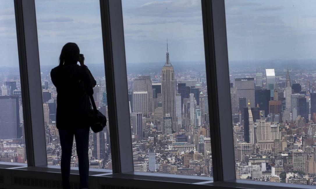 Vista. Mulher fotografa Nova York do 100º andar do One World Trade Center: prédio marca a revitalização da Baixa Manhattan. Ao lado, jornalistas observam o Sky Portal, que mostra imagens da rua em alta definição Foto: MIKE SEGAR/REUTERS