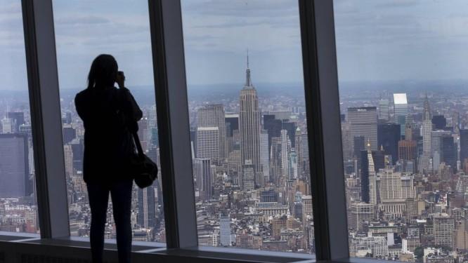 Vista. Mulher fotografa Nova York do 100º andar do One World Trade Center: prédio marca a revitalização da Baixa Manhattan. Ao lado, jornalistas observam o Sky Portal, que mostra imagens da rua em alta definição Foto: MIKE SEGAR / MIKE SEGAR/REUTERS
