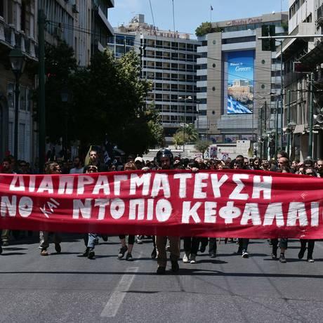 """Gregos protestam contra acordo com credores: """"não a negociações com capital nacional ou estrangeiro', diz a faixa Foto: LOUISA GOULIAMAKI/AFP"""