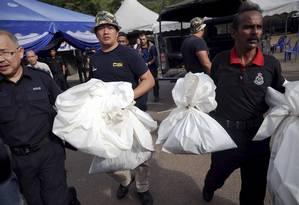 Policiais forenses carregam sacos com restos humanos encontrados em campos de traficantes na Malásia Foto: DAMIR SAGOLJ / REUTERS