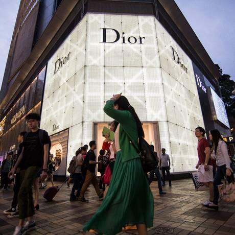 Pedestres caminham em frente a uma loja da marca francesa Dior em Hong Kong Foto: Billy H.C. Kwok/18-4-2015 / Bloomberg News