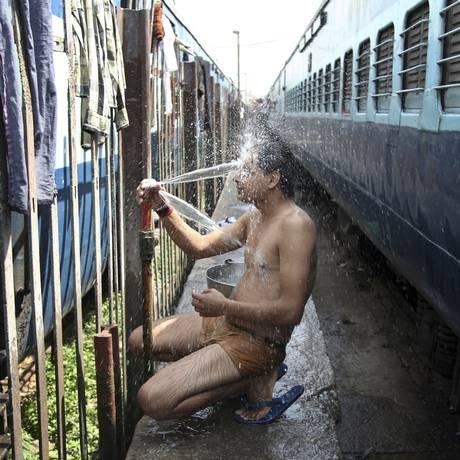 Passageiro indiano toma banho de mangueira em um dia quente de verão em uma estação de trem em Jammu, na Índia Foto: Channi Anand / AP