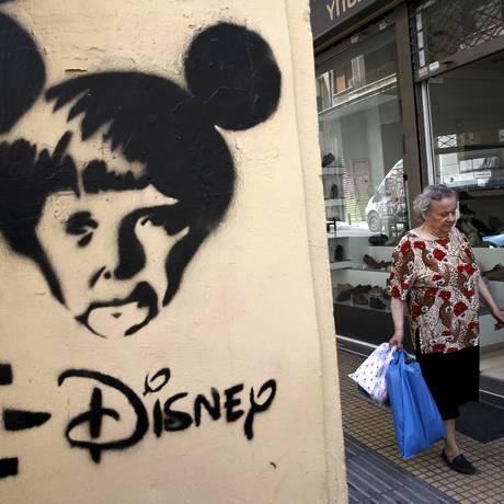 Imagem da chanceler alemã Angela Merkel com orelhas de Mickey Mouse em parede em Atenas Foto: ALKIS KONSTANTINIDIS / Reuters