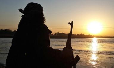 Jihadista vê o por do sol com sua AK-47 diante do Eufrates, em Raqqa Foto: Militant website / AP