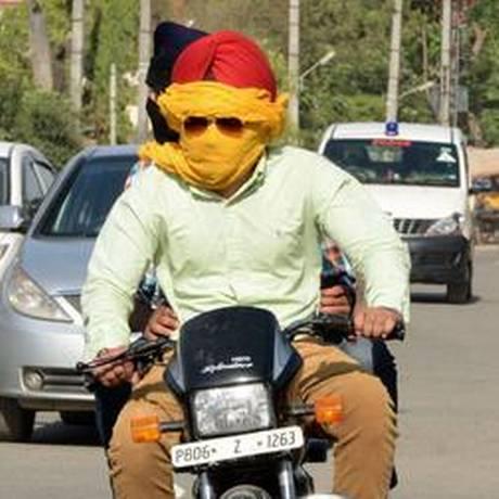 Motoqueiro indiano se protege do calor em Amritsar Foto: AFP
